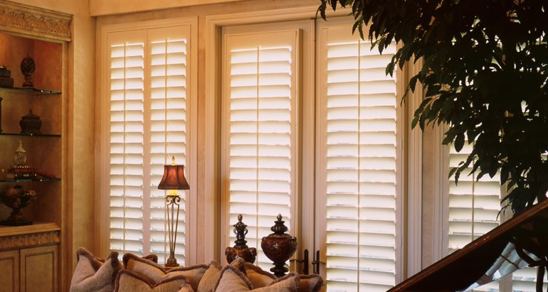 Plantation shutters on windows and door in Salt Lake City parlor