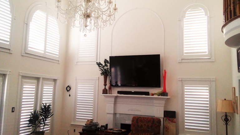 Salt Lake City great room with mounted television and arched windows.