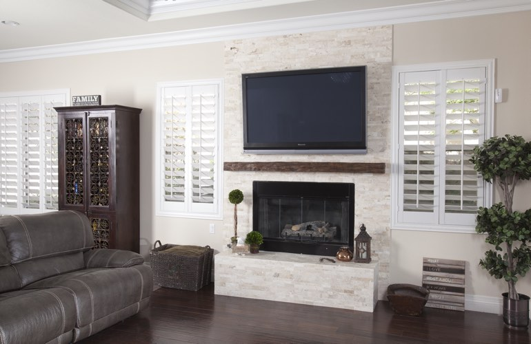 White plantation shutters in a Salt Lake City living room with solid hardwood floors.