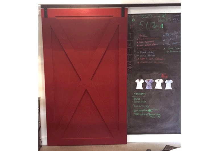 Red barn door with black hardware next to chalkboard