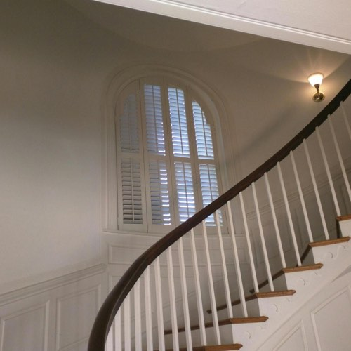 White plantation shutters adorning rounded window located in curved stairwell.