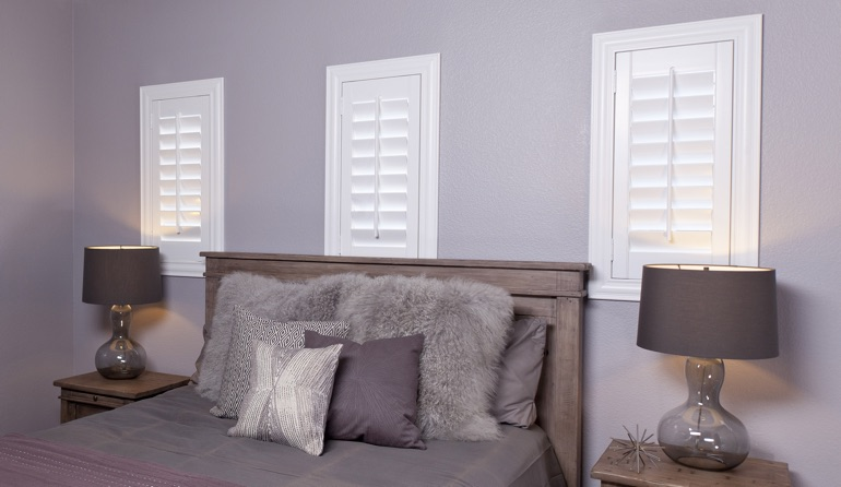 White plantation shutters in Salt Lake City bedroom windows.